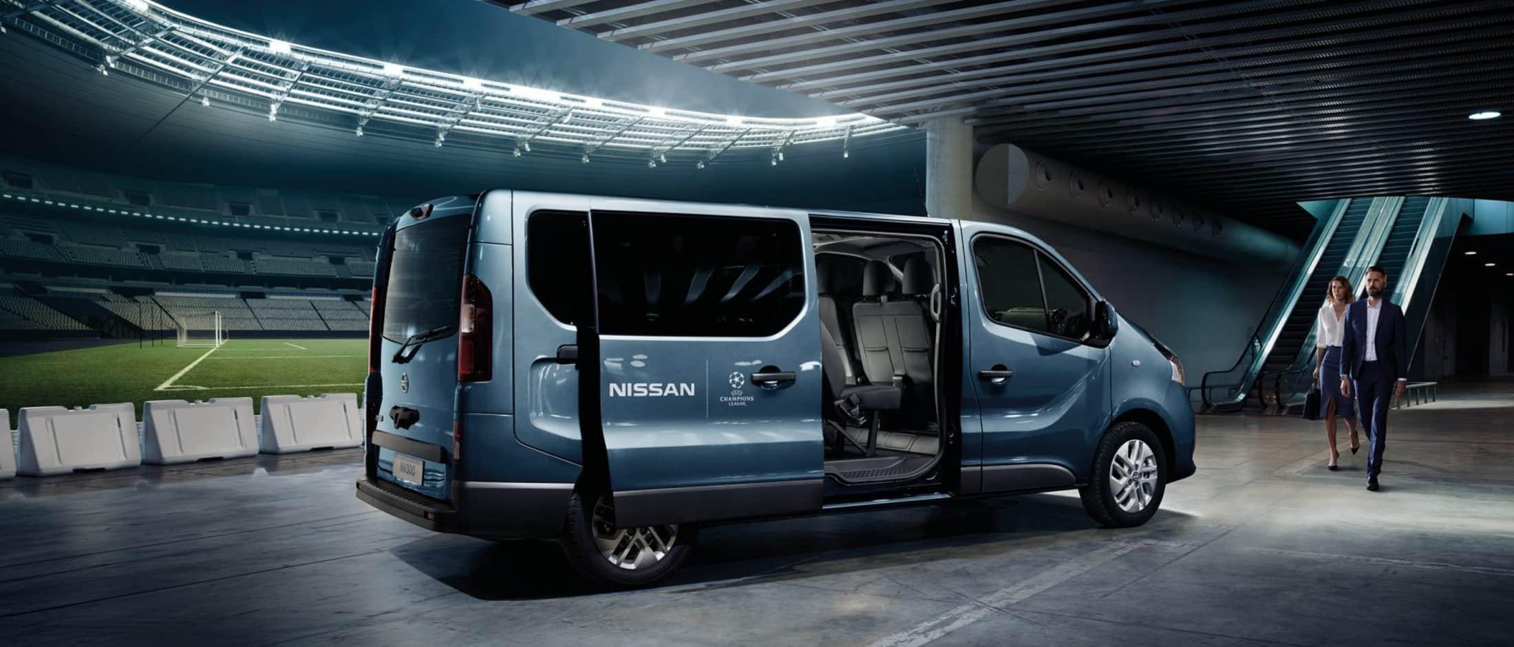 En blå Nissan NV300 står parkert ved en fotballbane. Den har Nissan logo på sidedøren, og det er to personer på vei mot bilen.
