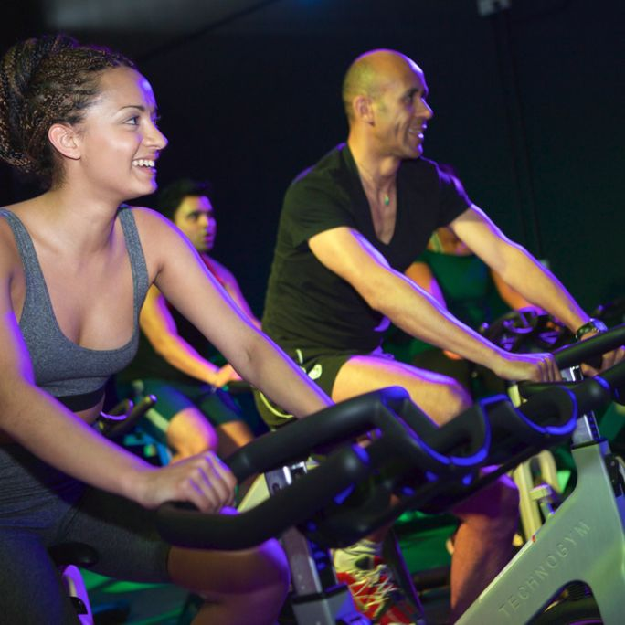 Two people riding indoor bikes