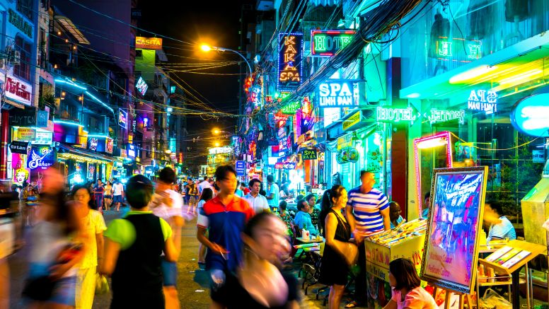 neon lights and bustling street market at night in saigon