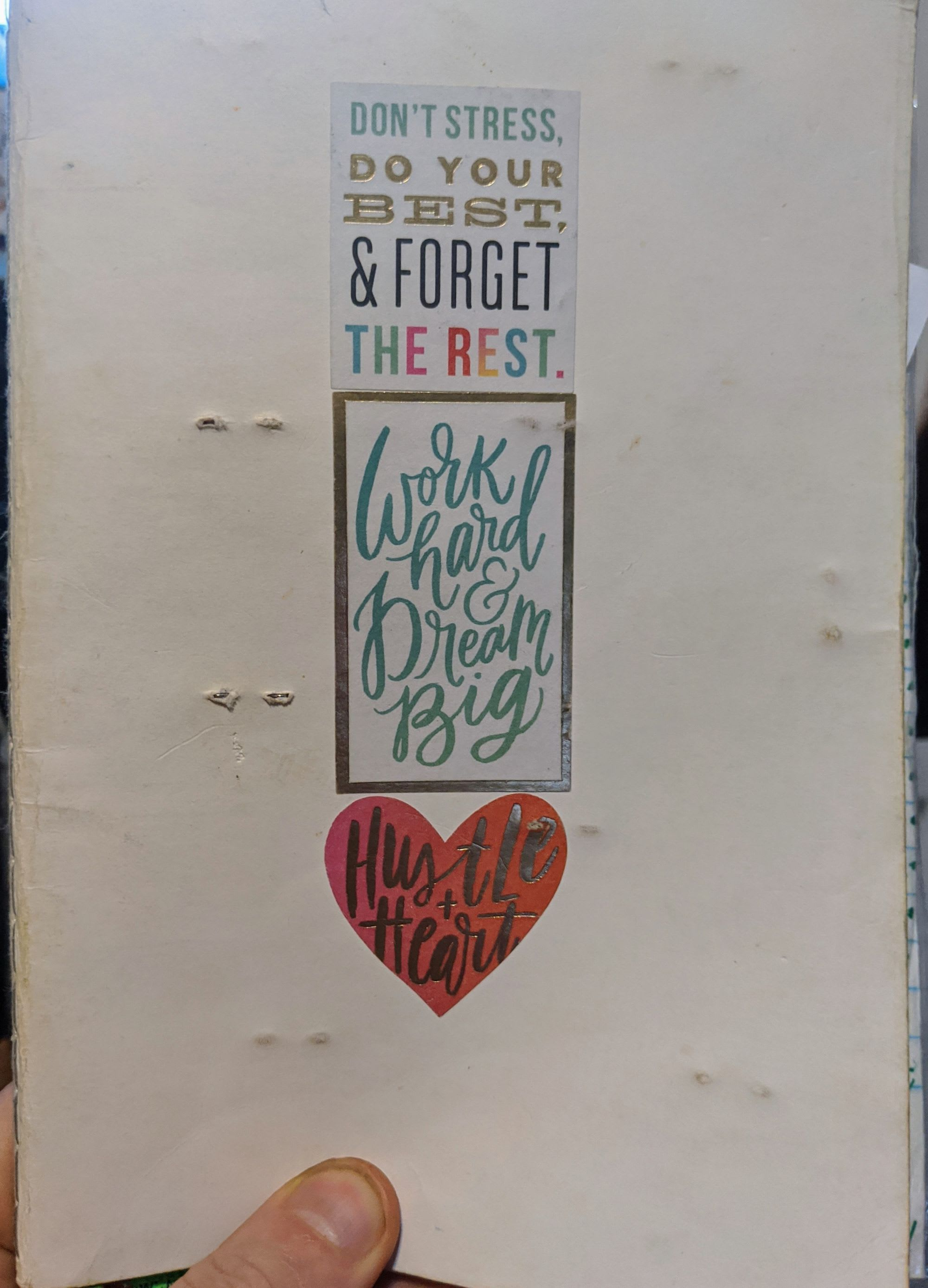 "Cover of a bullet journal with stickers that say, ""Hustle and Heart"", and ""Work Hard and Dream Big""."