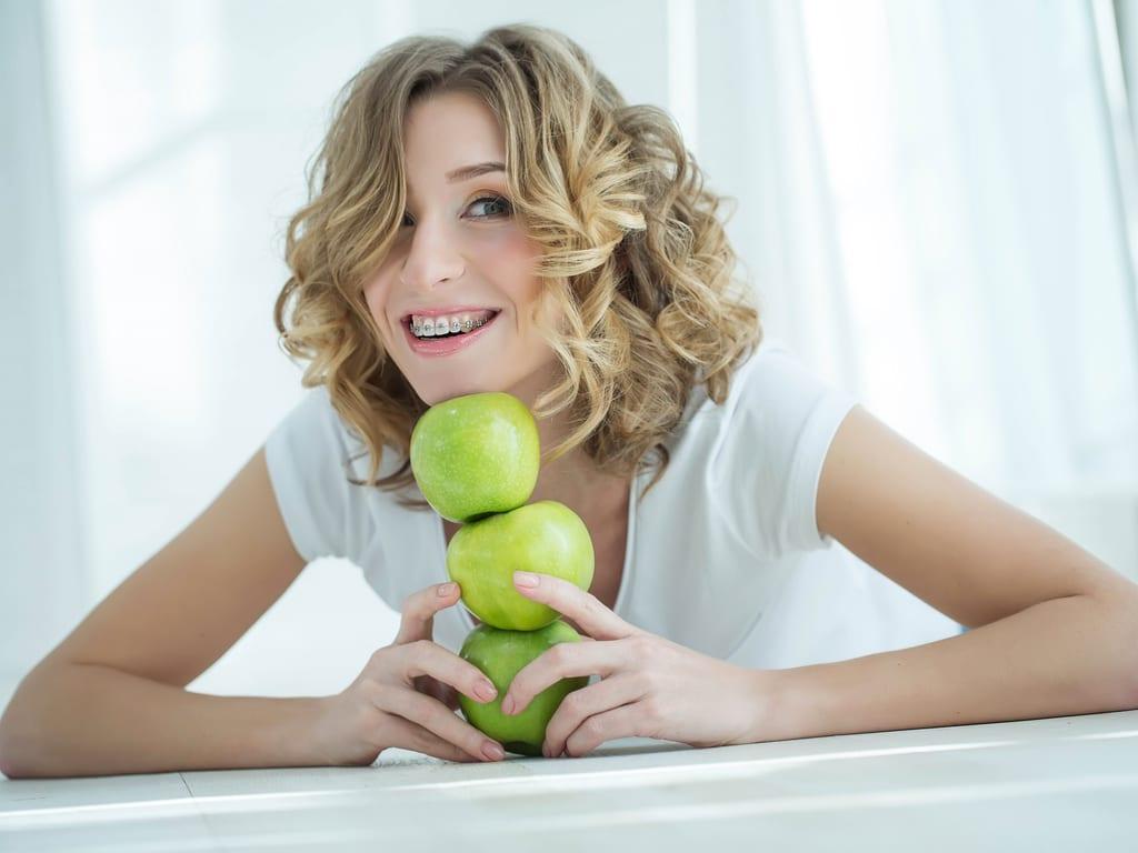 femme avec attaches dentaires tete sur des pommes