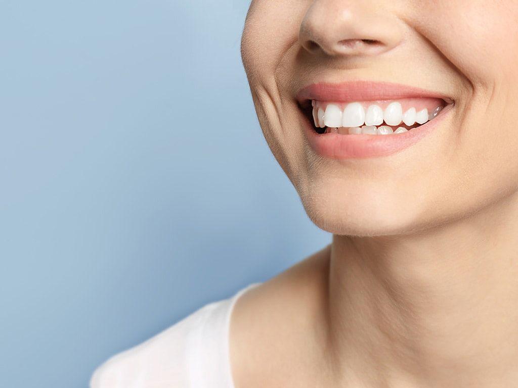 femme_montrant_son_sourire_sur_fond_bleu