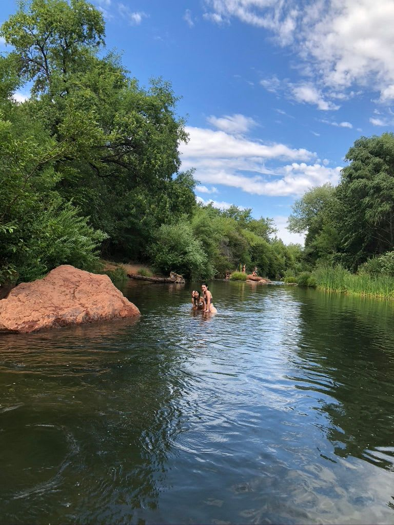 three girls in the water at Buddha Beach in Sedona with green bushes and red rocks