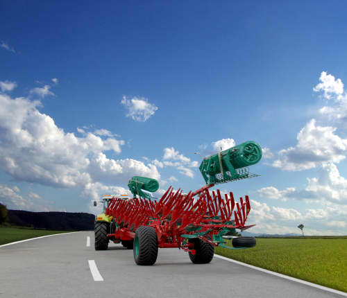 Packers - Kverneland Packomat compact and transported above ground level, dragged by tractor in a folded shape