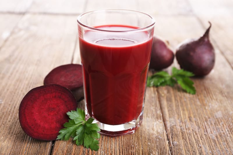 beet juice in glass on wood table with beets