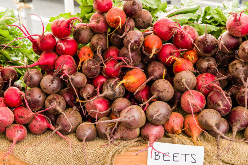 lots of raw garden beets on wood table with beets sign