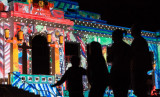 Visitors at a previous year's Enlighten Festival view the projections on the front of Old Parliament House.