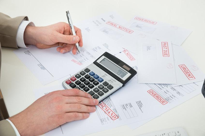 Businessperson Hand Calculating Bills