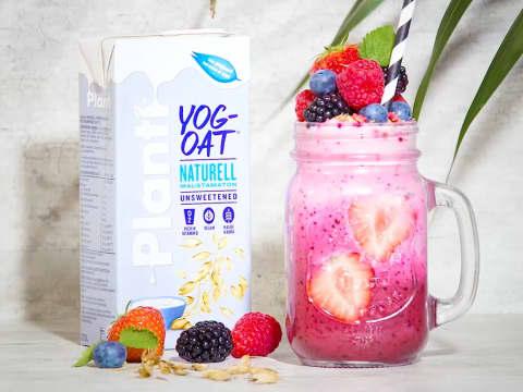 Rosa smoothie i glas med frukt på toppen