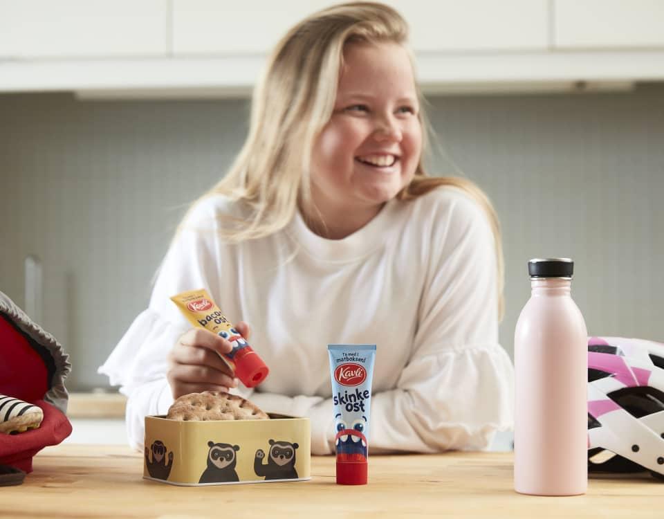 En smilende ung jente pakker matpakken sin til skoledagen. Hun holder en tube med Kavli BaconOst, som får plass i matboksen.