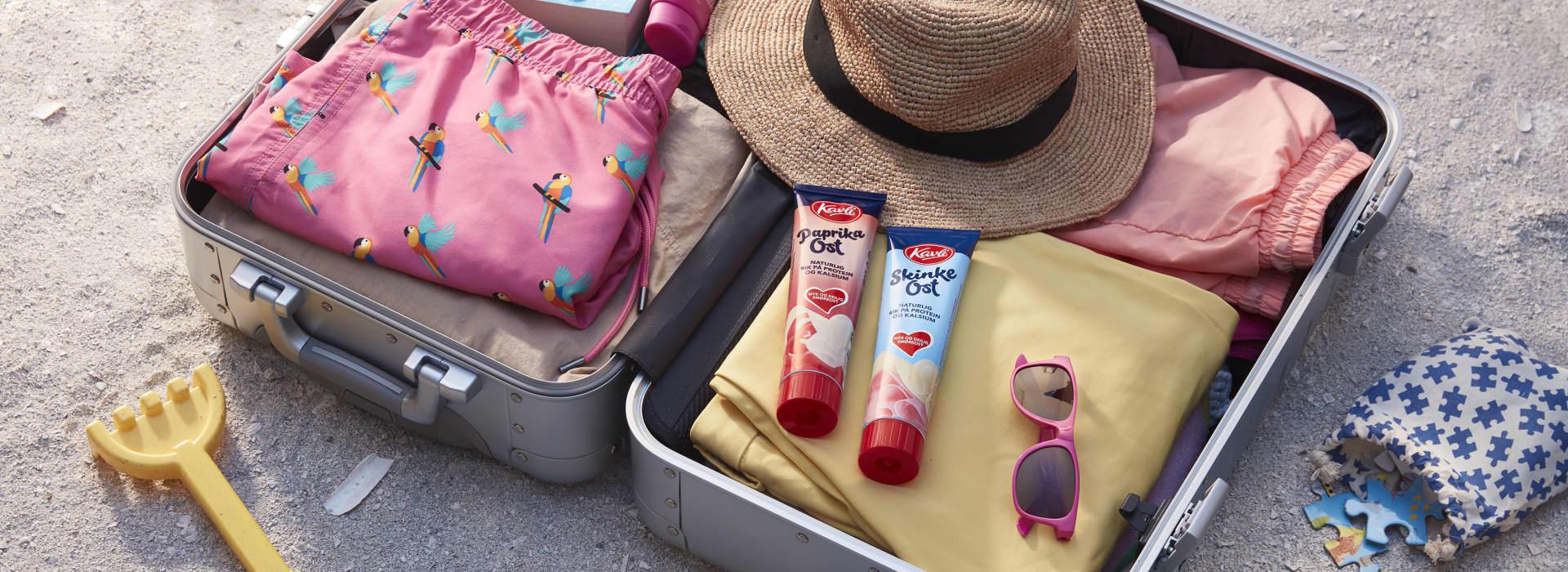 Fullpakket feriekoffert med klær, lesestoff, solkrem, solhatt og Kavli smøreoster på tube.