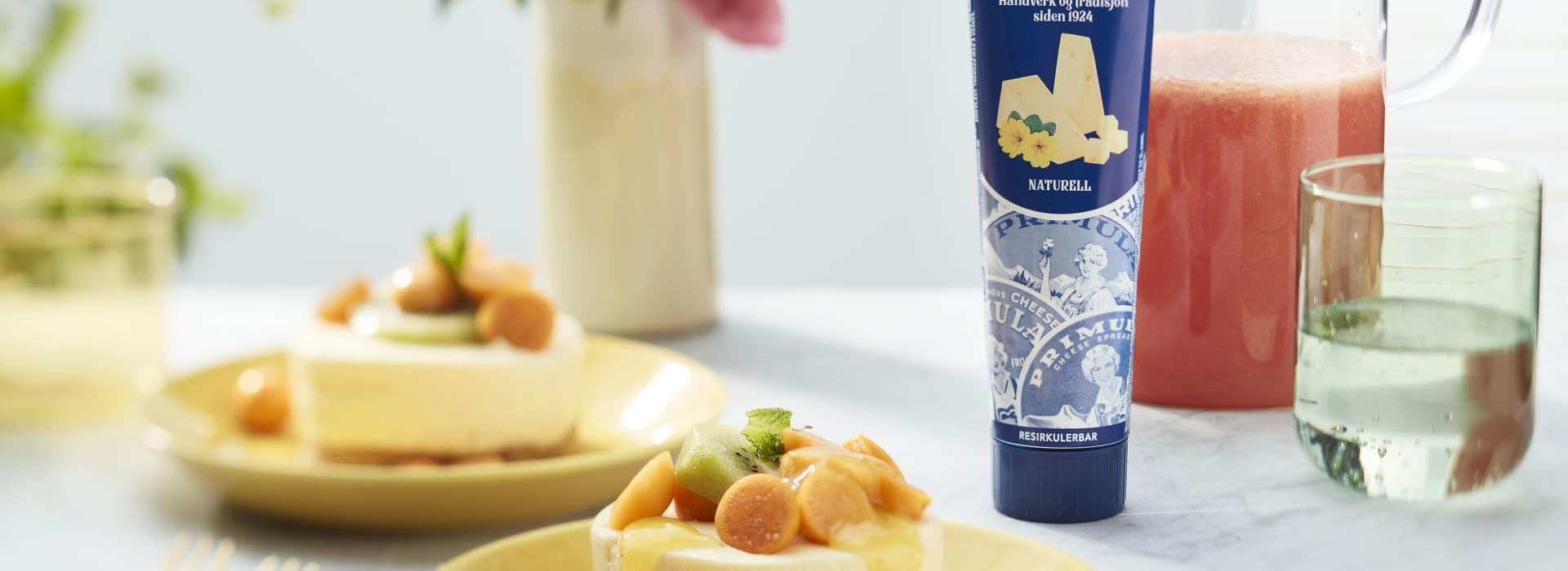 Sitronostekake i porsjoner, toppet med kiwi, physallis-frukt og en frisk, gul saus