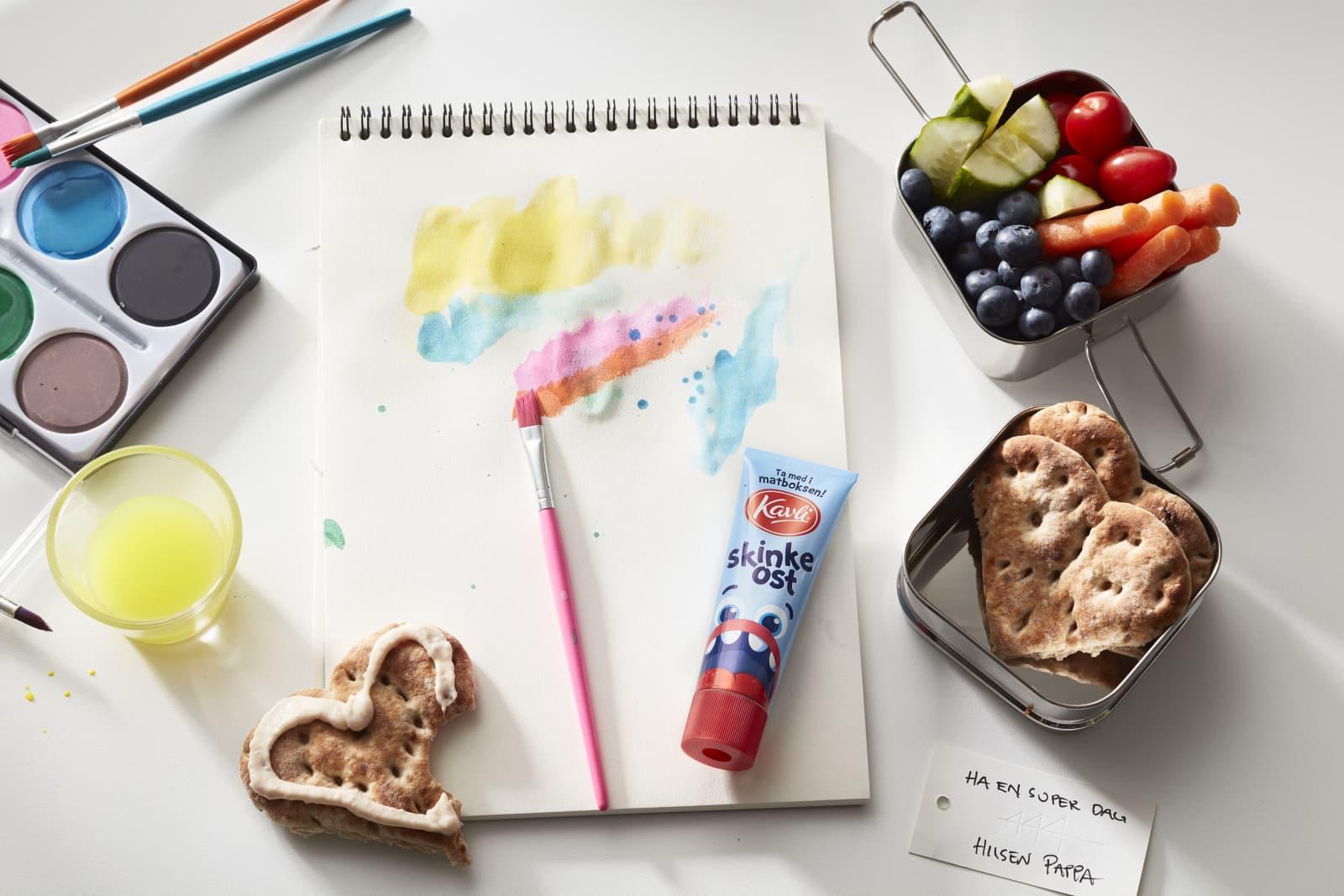 Matpakke og malesaker på skolepulten. Polarbrødhjerter med Kavli Skinkeost på, sammen med oppkuttet frukt og grønt og en liten smøreosttube.