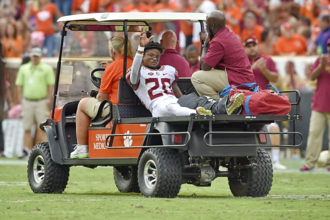Florida State receiver Keyshawn Helton waves to teammates while being carted off the field last October at Clemson.