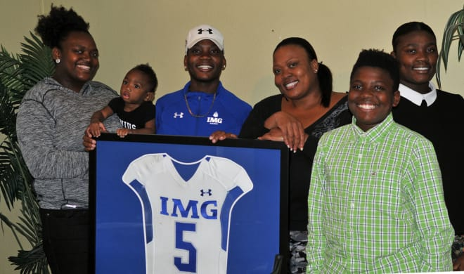 Janice Francois, four children and grandson pose for a portrait around Deondre's framed IMG Academy jersey.