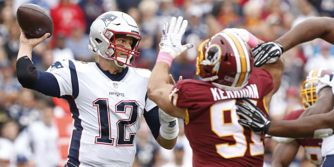 New England Patriots quarterback Tom Brady (12) passes the ball as Washington Redskins outside linebacker Ryan Kerrigan (91) chases in the second quarter at FedExField.