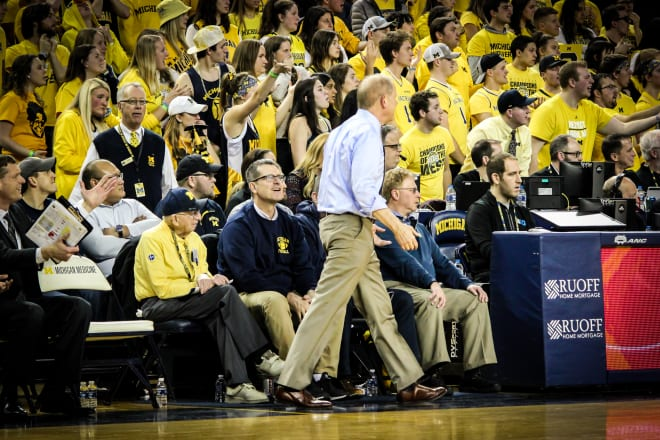 Beilein works while Harbaugh and booster Al Glick look on.