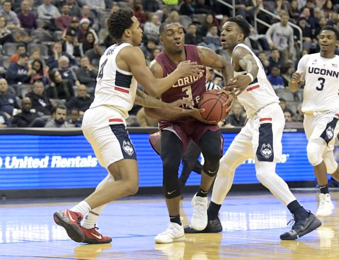 FSU guard Trent Forrest tries to fight his way through two UConn defenders on Saturday.