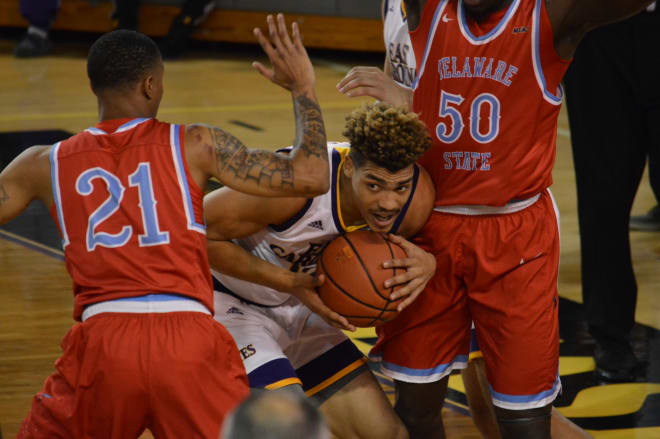 ECU's Aaron Jackson looks for room to maneuver between Delaware State's Saleick Edwards and Demola Onifade.