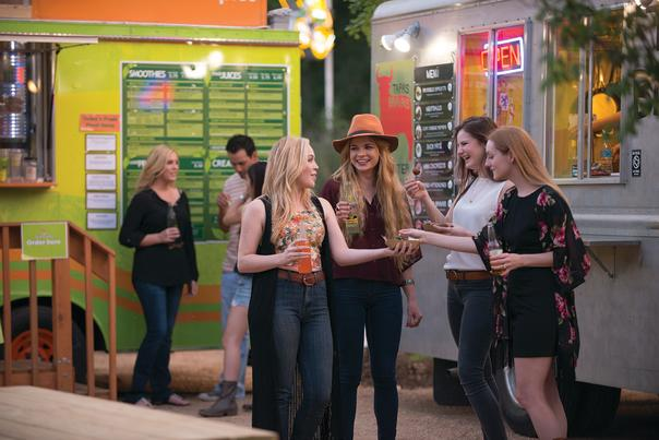 Four women share a meal at an Austin food truck park