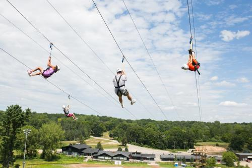 People riding the Cannonsburg Ski Area zip line