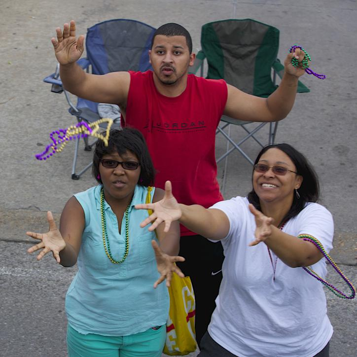 Adults catching beads at Mardi Gras