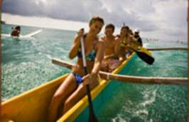 Friends paddling in a boat on the ocean.