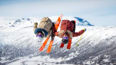 Two people with twin tip skis jumping together in one of Geilos terrain parks