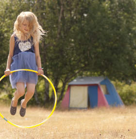 Girl jumping in front of tent