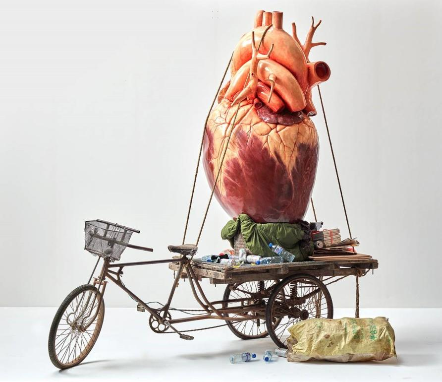 Recyling - Bao Yiluo. Recycling is an enormous fibreglass human heart tied onto the back of a san lun che, a popular multi-purpose tricycle often used for carrying recycled paper, cardboard and firewood in China. Thousands of organs are transplanted in China every year, but the lack of reliable information about their source raises serious ethical and legal questions. This work is part of the White Rabbit Collection, Sydney. Image: Courtesy of the artist and White Rabbit Collection, Sydney