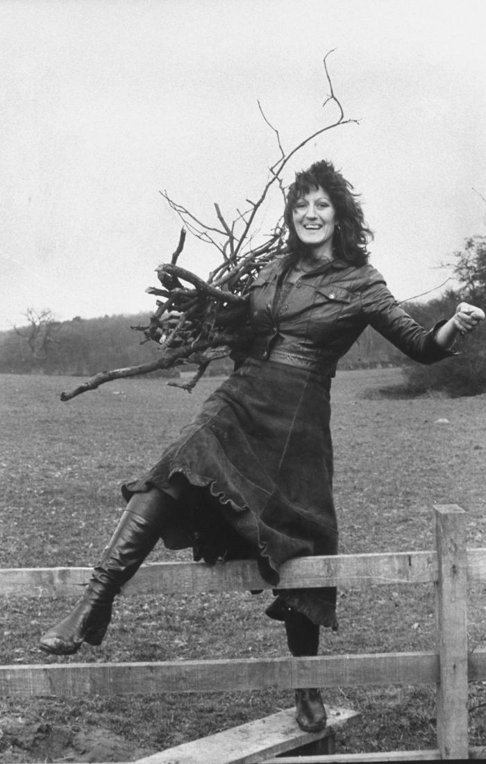 """Germaine Greer collects firewood. LIFE ran this caption: """"In the English countryside near Warwick University, she teeters across a fence while collecting wood for her apartment fireplace"""". Picture: Terence Spencer/The LIFE Picture Collection/Getty Images."""