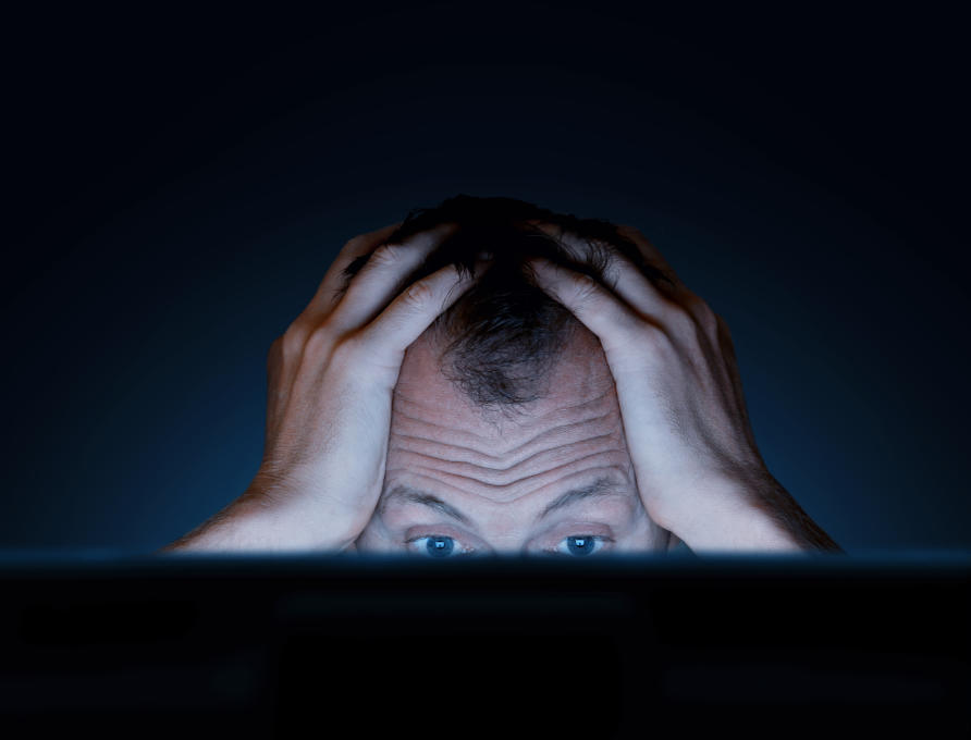 Man looking at computer screen with hands on this head in frustration